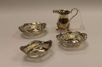 A silver cream jug, Birmingham 1972, together with three silver dishes with pierced decoration, 138.7g. (4)