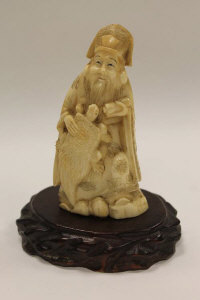 An early twentieth century carved ivory figure depicting a robed gentleman holding a turtle, on stand, height 13 cm.