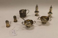 Two pairs of silver pepperettes, together with a pair of silver salts with spoons and a silver mustard pot. (7)