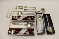 Three silver spoons with golfing terminals, together with a pair of silver sugar nips, three silver teaspoons and a silver spoon with pusher. (10)