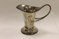 A silver Arts & Crafts style cream jug by George Unite, height 10 cm.