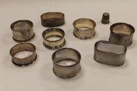 Eight silver napkin rings, together with a silver thimble.  (9)