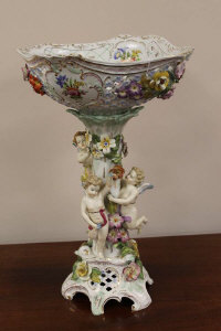 A continental porcelain encrusted comport surmounted with cherubs, height 46 cm.