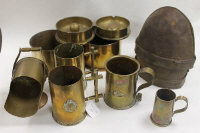 A collection of WW I brass trench art including tankards, scuttle and shells, together with a pair of early metal helmets. (11)