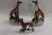A pair of nineteenth century Staffordshire greyhound models, height 31.5 cm, together with another flat backed greyhound figure of the same era. (3)