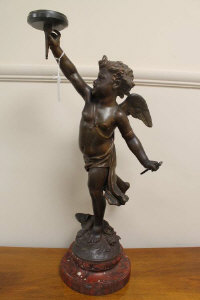 A spelter figured lamp depicting a cherub, on rouge marble socle, height 62 cm.