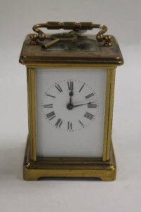 A brass carriage clock with enamel dial, height 11 cm.