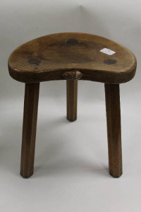 A carved oak three legged stool by Robert 'Mouseman' Thompson of Kilburn.