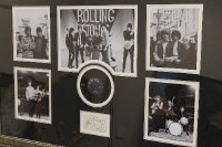 "A montage relating to the Rolling Stones, comprising five monochrome images, mounted with a vinyl 7 "" single and a page signed by the band members, 80 cm x 120 cm, framed."