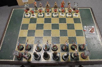 A thirty two piece Tower of London 900th anniversary chess set, on oak refectory board table fitted with a drawer.