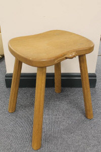 A carved oak four-legged stool by Robert 'Mouseman' Thompson of Kilburn.
