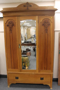 An Edwardian walnut mirror door wardrobe fitted with a drawer, width 136 cm.