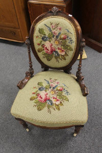 A Victorian walnut nursing chair with tapestry seat.