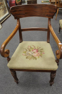 A Victorian mahogany armchair with upholstered tapestry seat.