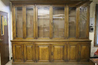An Edwardian oak library bookcase, the six glazed doors above six panelled cupboard doors below, width 310 cm.