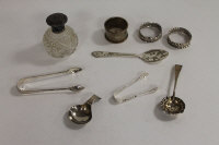 Three silver napkin rings, together with five items of silver cutlery and a silver topped bottle. (9)