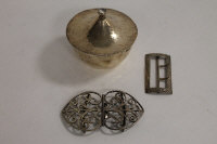 A silver two-piece belt buckle, together with another silver buckle and a planished white metal lidded pot. (3)