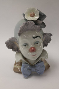 A Lladro china figure - A Clown head study, height 22 cm, with mahogany stand, boxed.