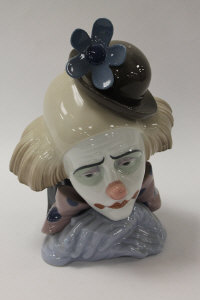 A Lladro china figure - Clown with bowler hat, height 27 cm, with mahogany stand, boxed.