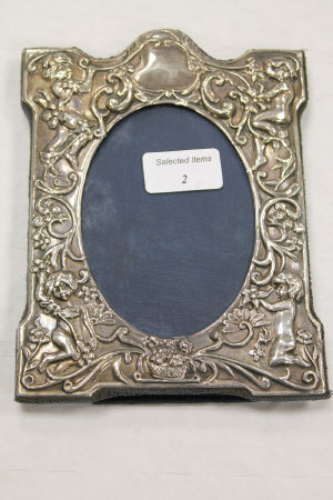 A silver embossed photograph frame, 15 cm x 19 cm overall.