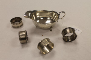 A silver sauce boat, Birmingham 1921, together with four silver napkin rings. (5)