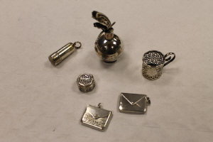 Two silver miniature stamp cases, together with a small silver flask, silver miniature cup holder, silver needle case and a miniature white metal pot. (6)