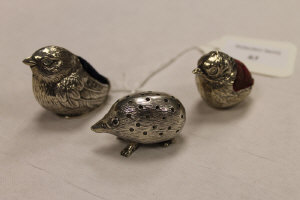 A silver novelty pin cushion depicting a hedghog, together with two others depicting birds. (3)
