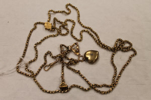 A 9ct gold guard chain upon which hangs a bow brooch, heart locket and citrine fob.