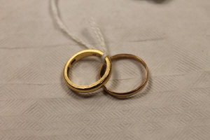 An 18ct gold wedding band, 4.3g, together with another yellow metal wedding band. (2)