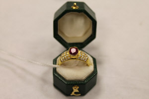 An 18ct gold ruby ring, approximately 1.08ct, with diamond encrusted shoulders.