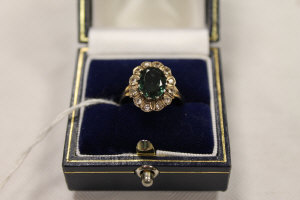 A diamond and tourmaline cluster ring mounted in yellow metal.