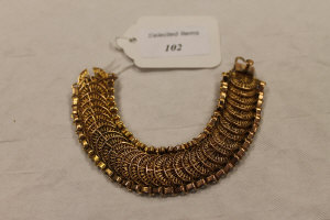 A yellow metal flexi-link bracelet with fan shaped filigree centres, 49g.