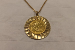 A 1963 gold sovereign, mounted in 9ct gold and suspended upon a flat trace chain.