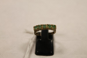 A 9ct gold emerald half hoop ring.