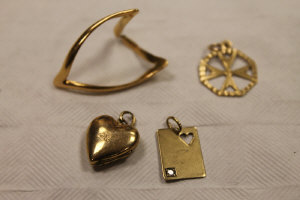 A 9ct gold card charm together with a yellow metal wishbone ring, a 9ct gold heart locket and a 9ct gold cross pendant. (4)