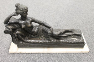 A French bronze figure depicting a lady reclining upon a couch, on marble plinth, width 46 cm.