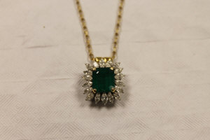 An 18ct white and yellow gold Columbian emerald and diamond pendant, suspended upon a 9ct gold chain.