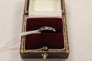 An 18ct gold diamond and sapphire half eternity ring.