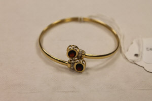 A 9ct gold bangle set with two diamonds and garnets.