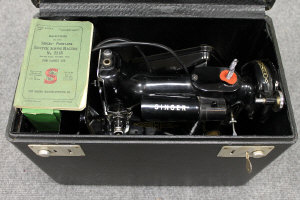 A Singer portable sewing machine model 221K, in original case with accessory kit.