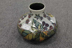 A Moorcroft pottery squat vase decorated with leaf and berries, height 16.5 cm.