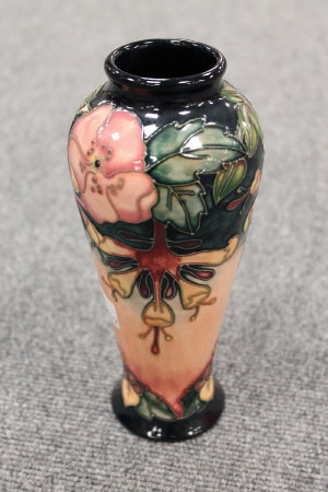 A Moorcroft pottery vase decorated with tubelined flowers on peach ground, height 21 cm.