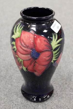 A Moorcroft tall vase decorated with amaryllis design, height 26 cm.