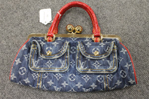 A Louis Vuitton denim and red leather hand bag.