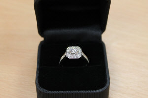 An 18ct white gold diamond cluster ring, approximately 1.1ct, colour G, with diamond shoulders.