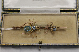 A 9ct gold spider bar brooch set with blue stones.