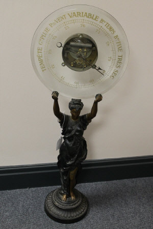 A French spelter figure, standing with crystal barometer aloft, signed with initials L.S.F., height 85 cm.
