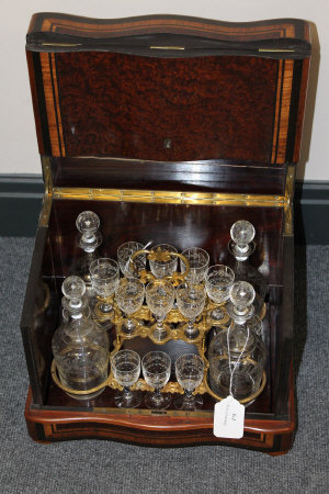 A late Victorian inlaid walnut decanter box, with fitted interior and etched glass decanters, width 34 cm.