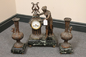 A three piece marble and spelter clock set. (3)