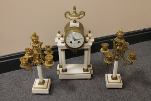 A three piece French white marble and ormolu clock set. (3)